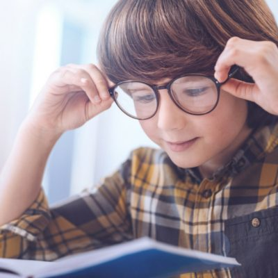 a young boy with glasses reading a book