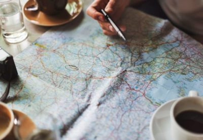 a cup of coffee and a hand with a pen above the world map on a table