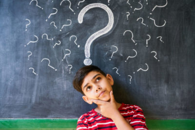 a boy with big question mark above his head